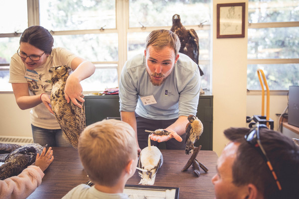 Museum volunteer Hannah Sonnenberg with husband and graduate student Ben Sonnenberg share some of the many artifacts housed at the Museum of Natural History with visiting children and their parents during the University's 2018 Day at the Museum event.