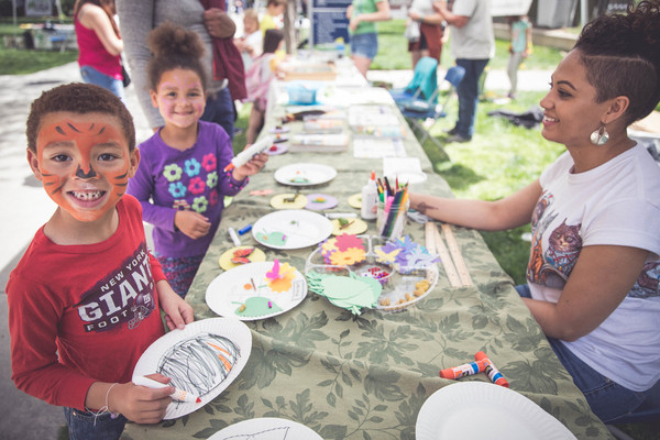 A brother and sister build bug ecosystems on paper plates outside the Museum.