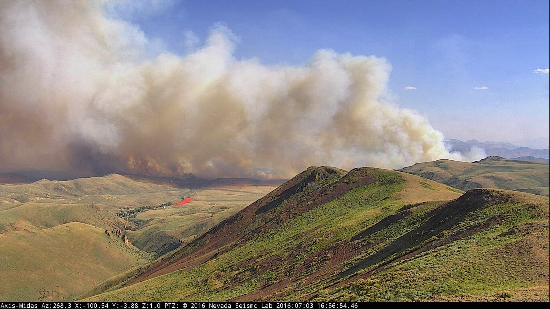 A wildfire's smoke column billowing up from a hill captured by the AlertWildfire camera system
