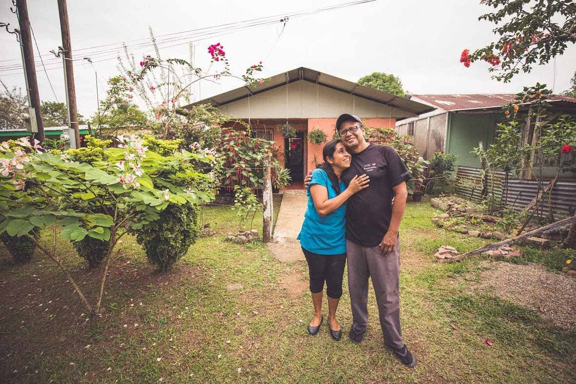 Humberto and Daysie Garcia in front of their home, which is surrounded by lush vegetation