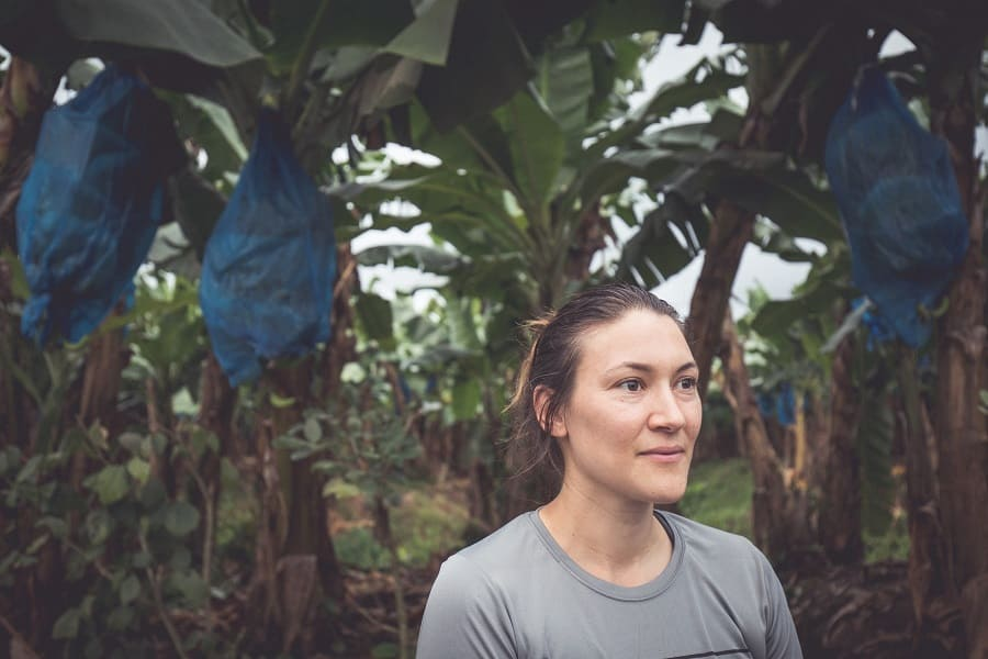 Dani Salcido standing in front of a row of banana trees