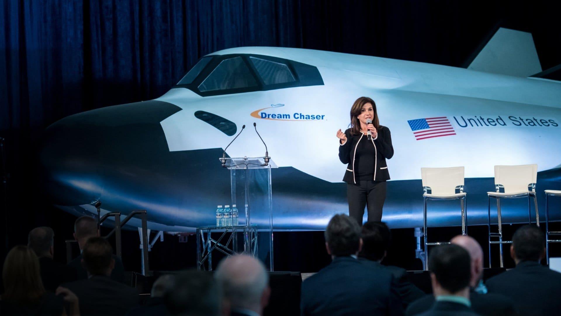 Eren Ozmen standing in front of the Dream Chaser spacecraft