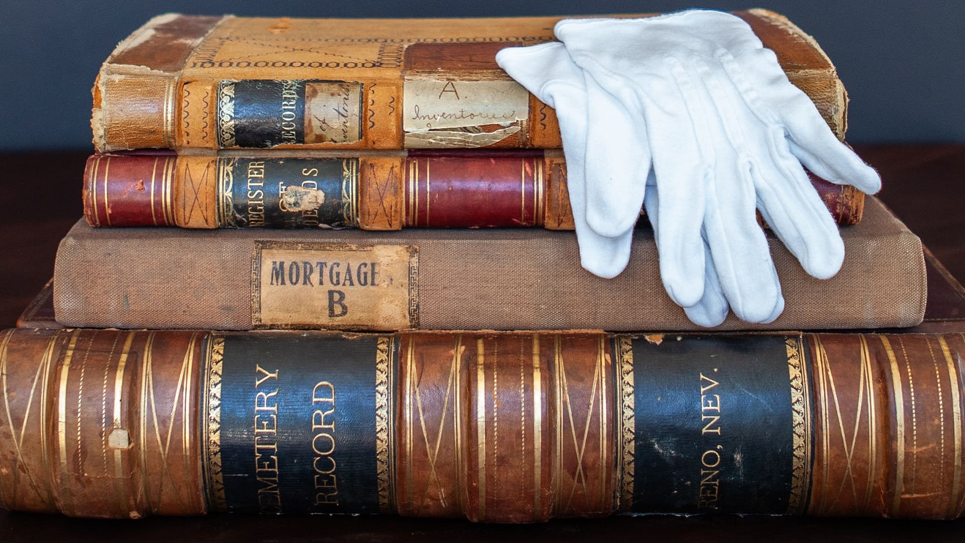 White gloves sit atop a stack of old books and ledgers from Reno's history