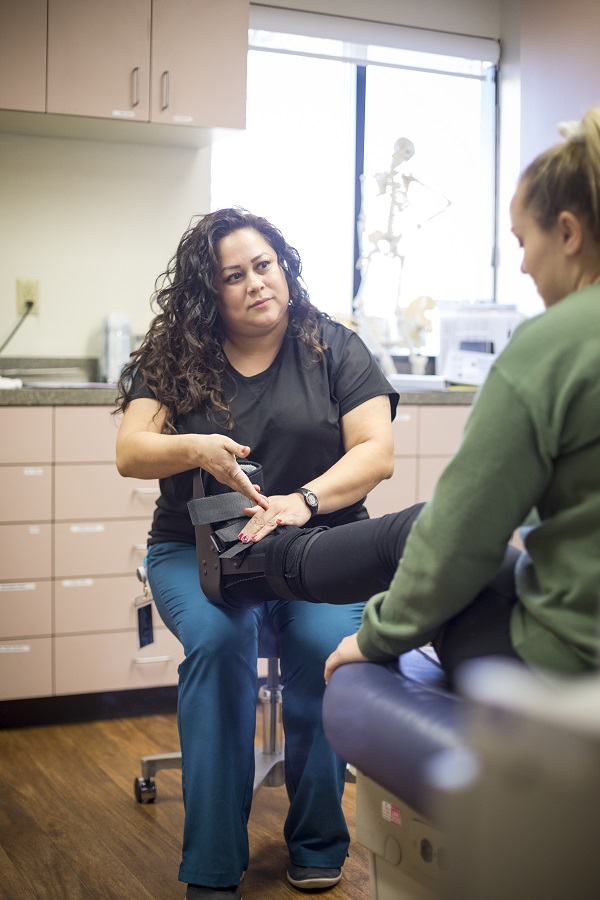 Crystal Rosas, SHC medicalassistant, fits a student with awalking boot.
