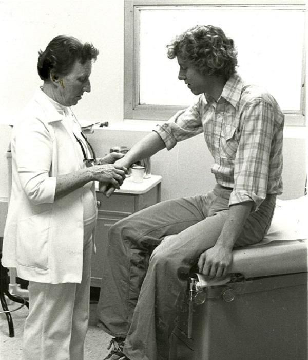 Rita Black examines a patient's wrist, 1979, black and white photo