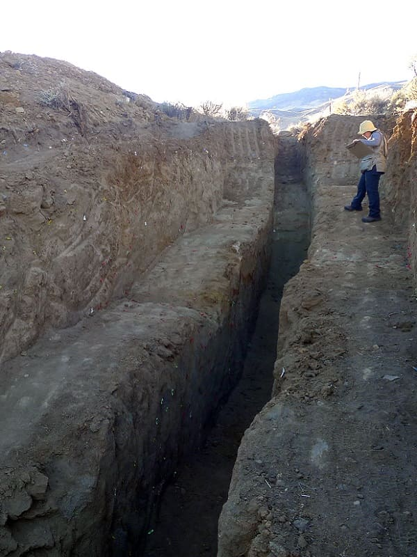 A geologist standing in the cleared out trench of the Ridgecrest fault