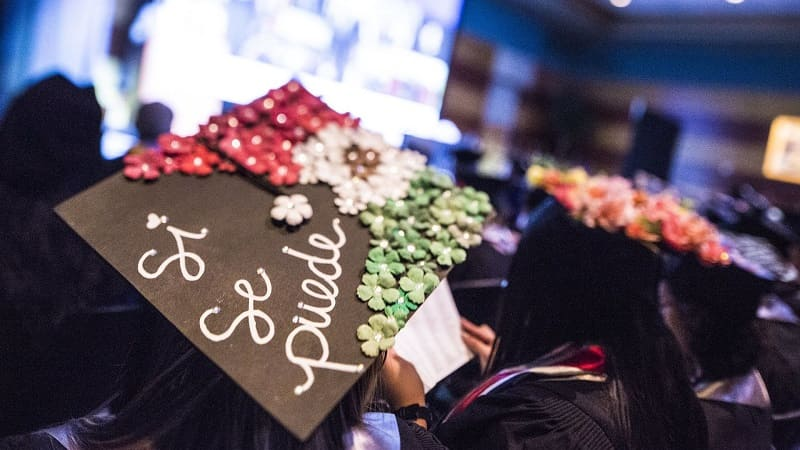 """A graduating student's mortar board reads """"Si, se puede"""""""