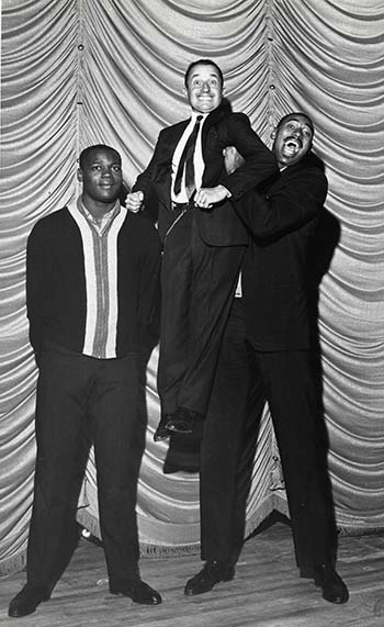"Basketball player Wilt ""the Stilt"" Chamberlain hoists John Ascuaga up to his height while his team member Howie Montgomery watches ("