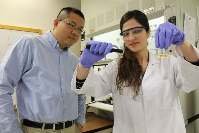 Female graduate student in lab coat shows substance in test tubes to male researcher