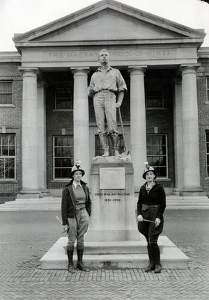 Two young women mining students in hardhats pose next Mackay statue, antique photo