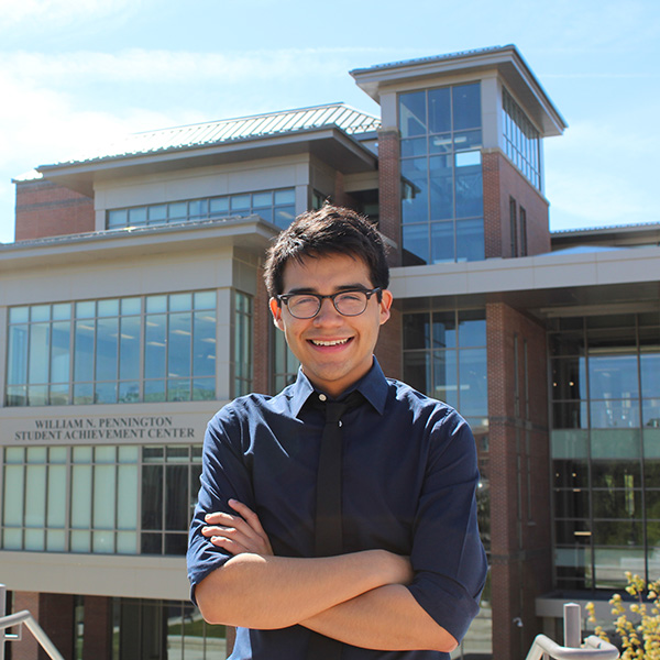 Josue Regalado in front of the Pennington Student Achievement Center