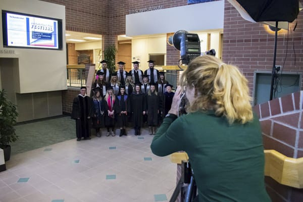 The photographer takes photos of the graduating class on the atrium steps.
