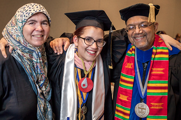A graduate with faculty members at the American Indian & Alaskan Native Graduate Celebration