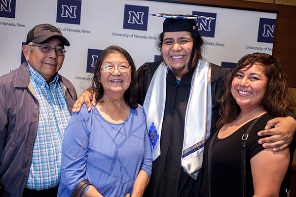 A smiling graduate with family members at the American Indian & Alaskan Native Graduate Celebration