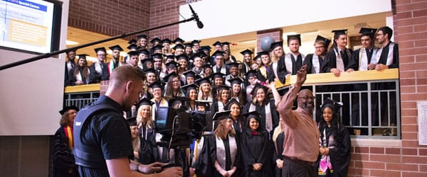 Students and faculty pose in regalia indoors while listening to Paul Mitchell.