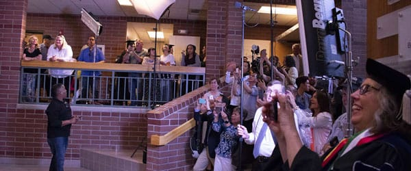 People take photos of the graduates in the Reynolds School atrium.