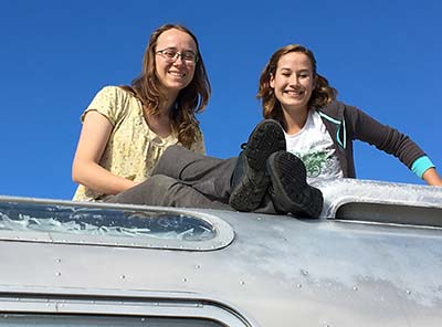 Allison Blair and friend sitting on top of airstream trailer