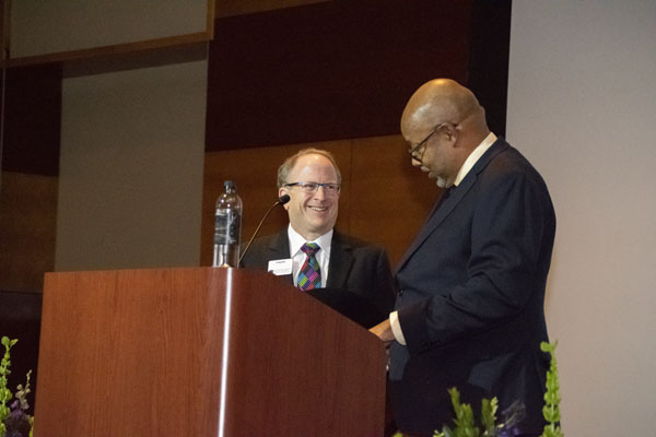 Leonard Pitts Jr. stands on stage next to dean Stavitsky.