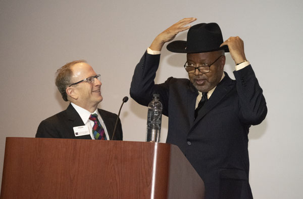 Leonard Pitts Jr. puts on a Stetson cowboy hat next to dean Stavitsky.