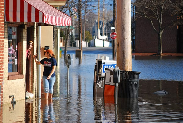 Woman walks through water on a flooded street.