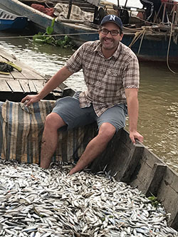 Zeb Hogan sits in boat with fish in Cambodia