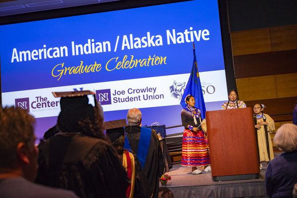 The crowd attends to speakers in traditional clothing at the American Indian & Alaskan Native Graduate Celebration