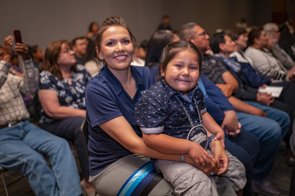 A smiling child sits on the lap of a student speaker at the American Indian & Alaskan Native Graduate Celebration