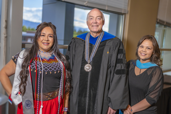 President Johnson posing with graduates at the American Indian & Alaskan Native Graduate Celebration