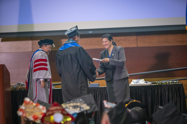 A graduate recieving honors on stage at the Asian American & Pacific Islander Graduate Celebration