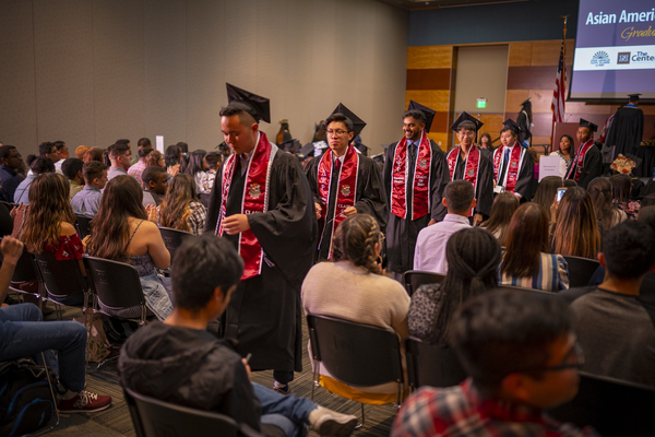 A line of graduates approaching the stage at the Asian American & Pacific Islander Graduate Celebration