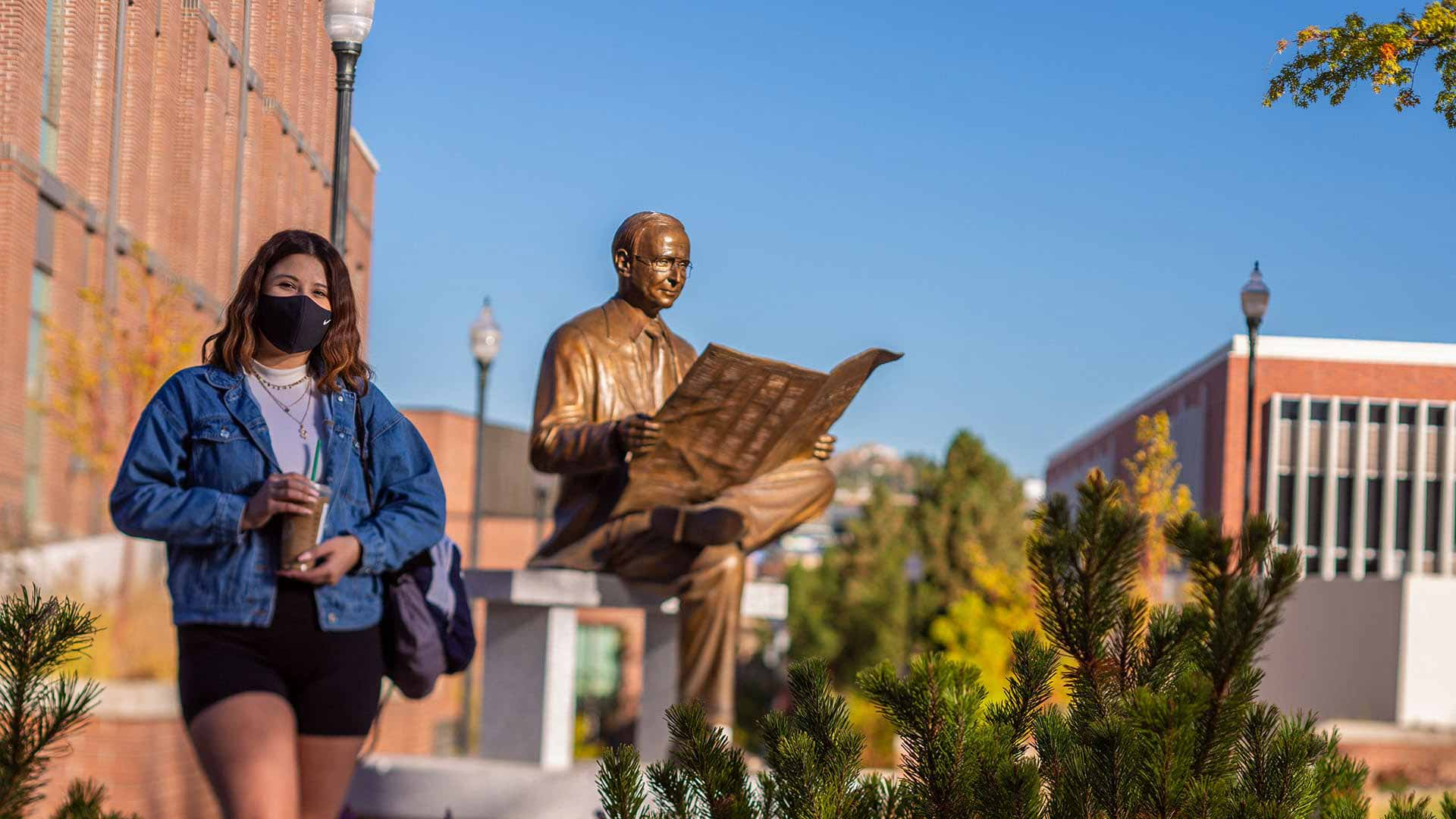 A student wears a mask and holds a coffee cup as they stand in front of the Senator Richard Bryan statute on the campus of the University of Nevada, Reno.