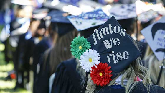 """A decorated cap at commencement says """"Juntos we rise"""" and is adorned by three daisy-like flowers, one green, one white and one red."""