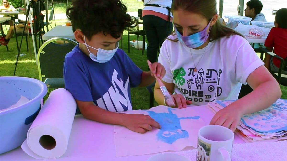 A 4-H youth, who is wearing a mask, is outside on a sunny day. He is sitting under a shade canopy at a folding table, holding a paintbrush. There is a roll of paper towels and a cup of paint-muddled water nearby. He's with a masked 4-H leader. They're working on a STEM project.