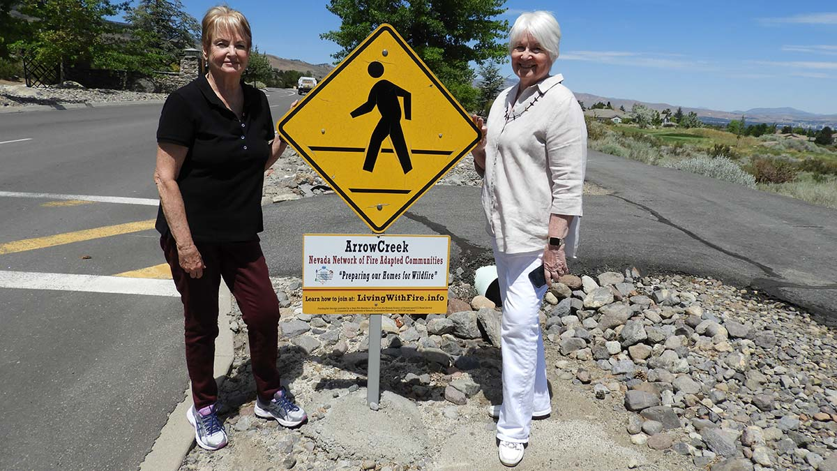 Kathi Delegal and Janet Ouren by Fire Adapted Community sign