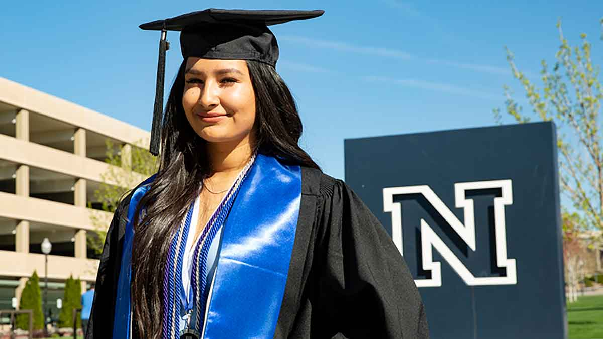 Lizeth Acosta in cap and gown and with cords