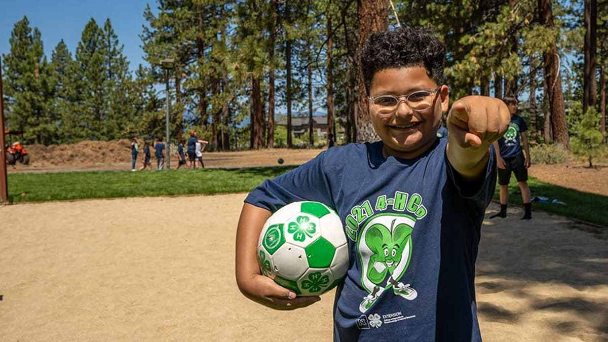 Child playing soccer at 4-H event.