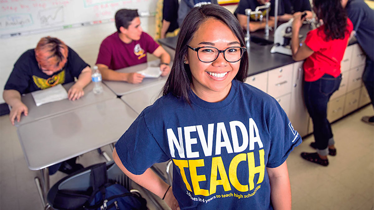 NevadaTeach student smiling with students in the background working on science project
