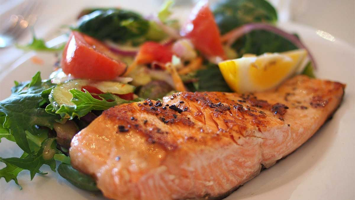 On a white plate is a freshly-prepared meal of seasoned, pan-seared salmon and a salad of leafy greens topped with cucumbers, tomatoes and onions. The dish is garnished with a lemon wedge.