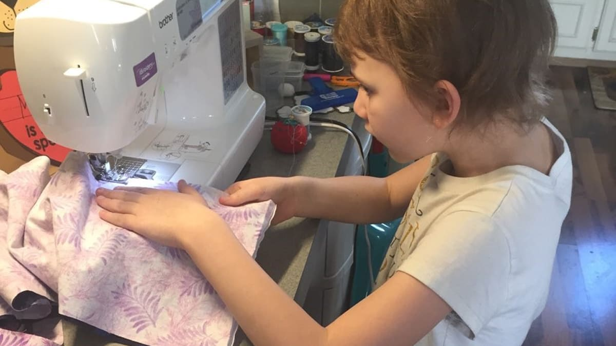 Young girl using a sewing machine to sew pink palm leaf printed cloth