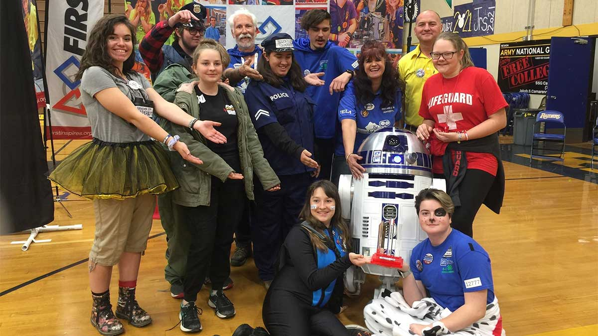 SuperBots and Awkward Silence team members, wearing various Halloween-like costumes, pose with R2D2 at championships
