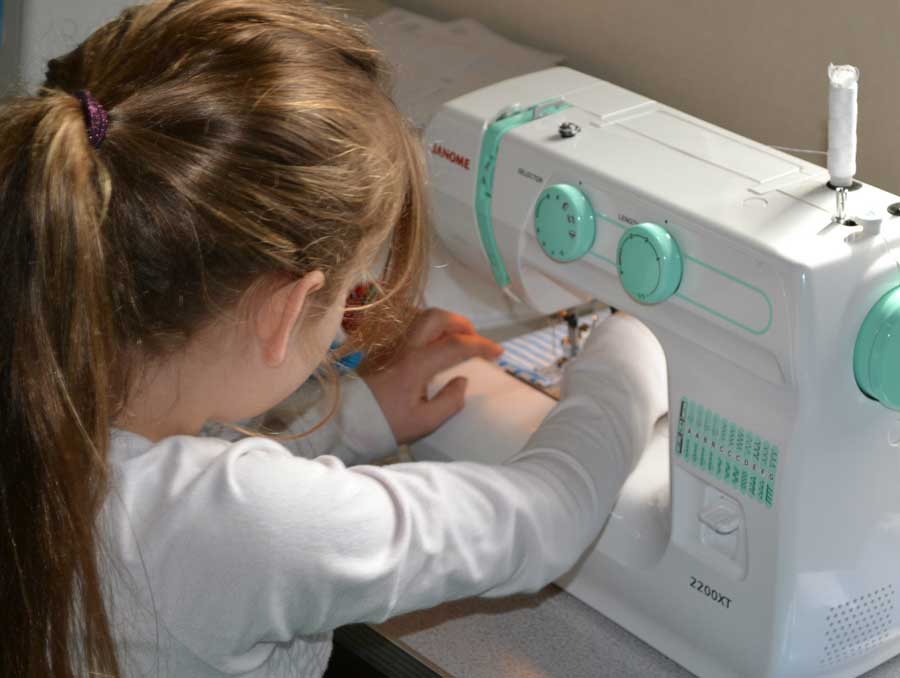 A girl using a sewing machine