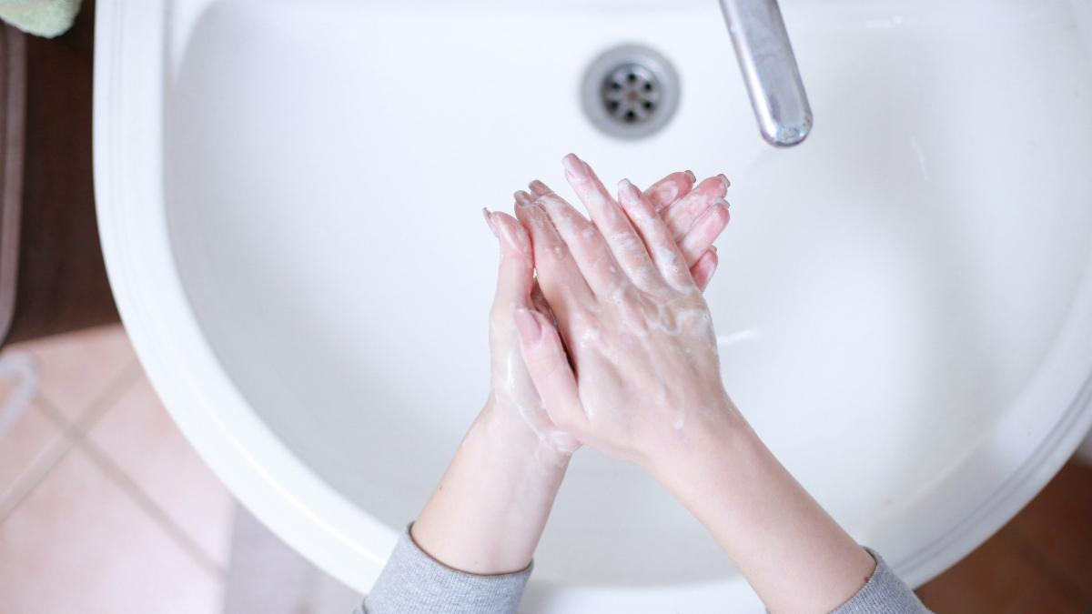 hands getting washed in a sink