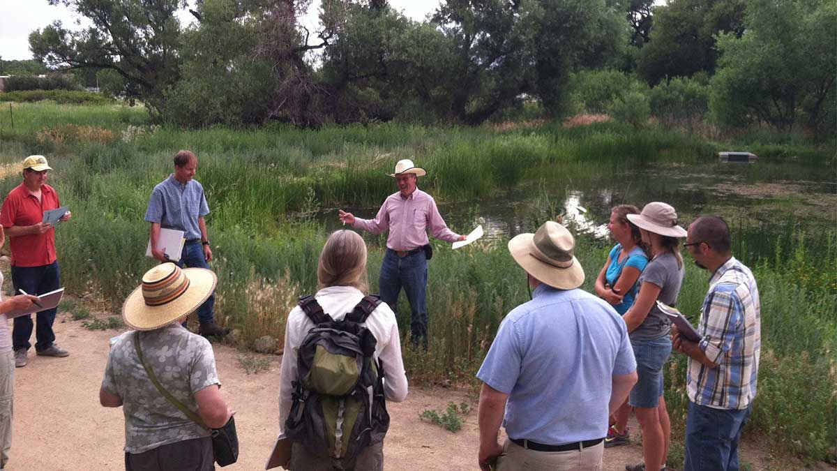 Sherm Swanson teaching a group of adults next to a pond