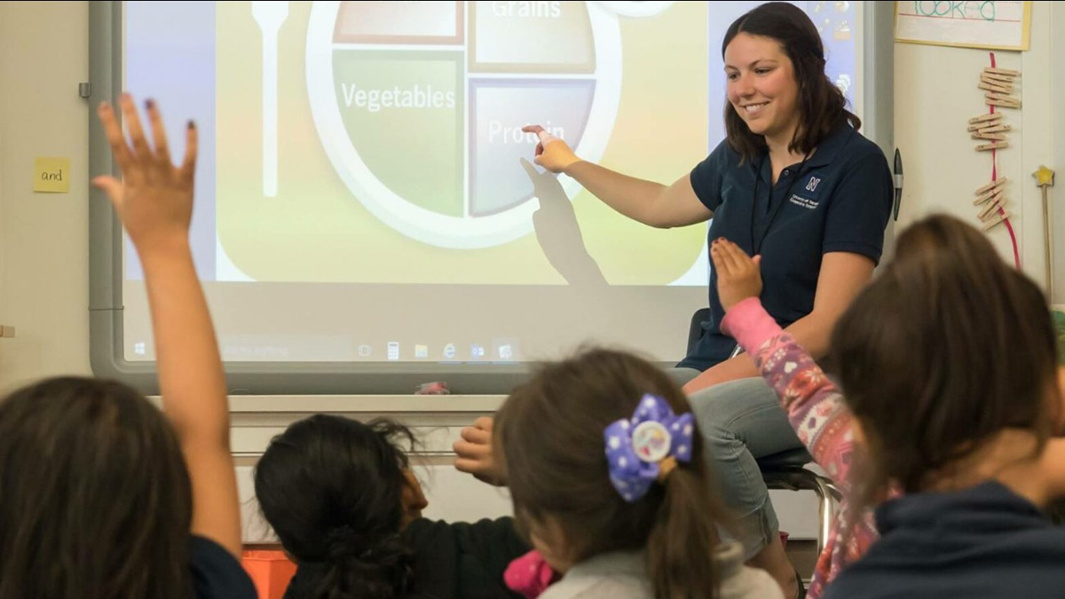 An Extension instructor pointing to the protein section of the MyPlate graphic as students raise their hands