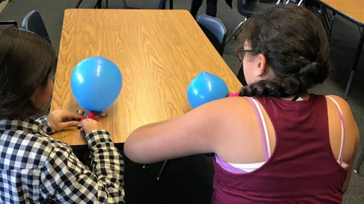 two students use balloons to race cars across a table