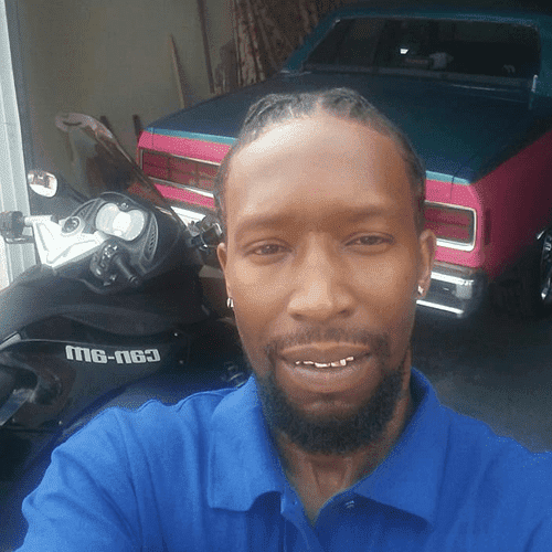 Cedric Bell near a motorcycle and sports car