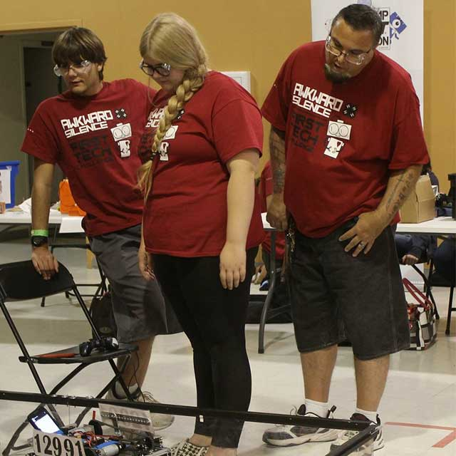 Jason Riendeau in an Awkward Silence 4-H Club shirt looks on as his club competes in a robotics competition