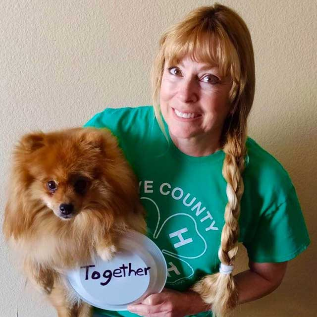 Lisa Remington in a Nye County 4-H shirt, holding a dog and a sign that says 'Together'