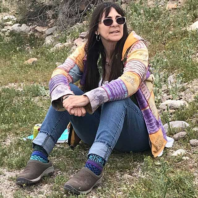 Robin Flinchum wearing sunglasses and a brightly colored sweater, sitting on the ground, arms around her knees