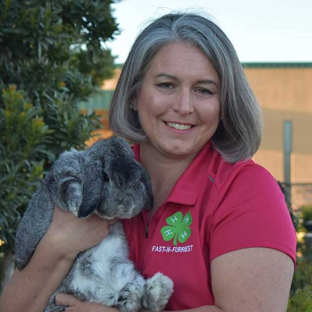 Susan Dreyfus, wearing a brightly colored Fast N Furriest 4-H shirt and holding a rabbit